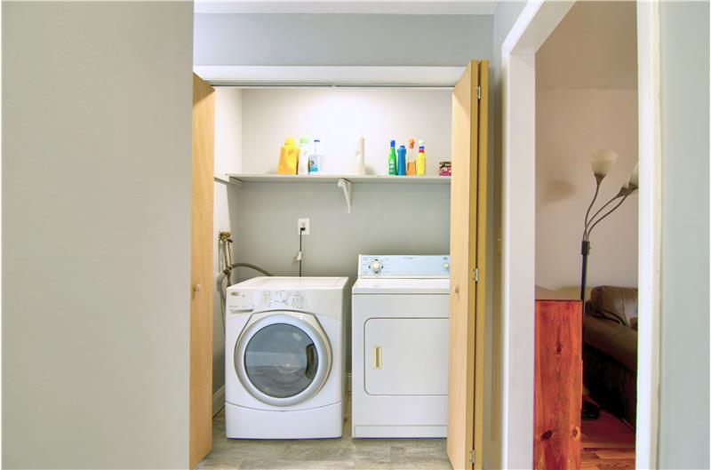 Laundry area in hallway behind doors