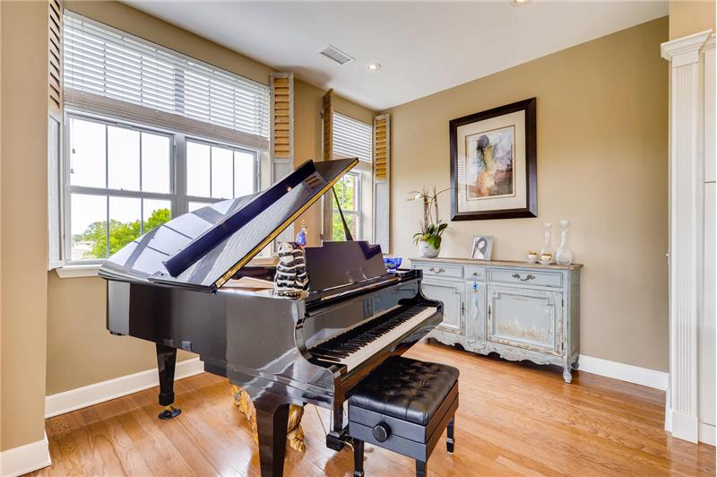 Spacious and sunny den with custom decorative shutters. Large enough for a grand piano.