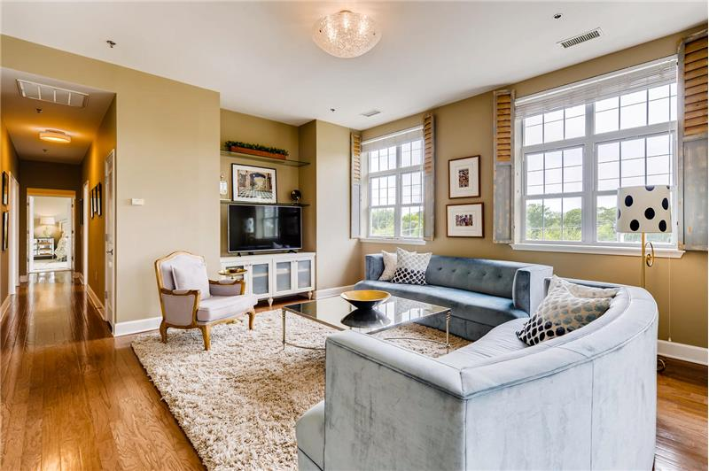 Spacious, sunny living room. Note the custom, decorative shutters.