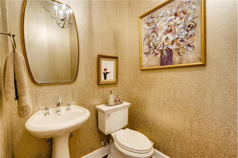 Elegant guest half-bath updated with designer wallpaper, mirror, chandelier, and new toilet.