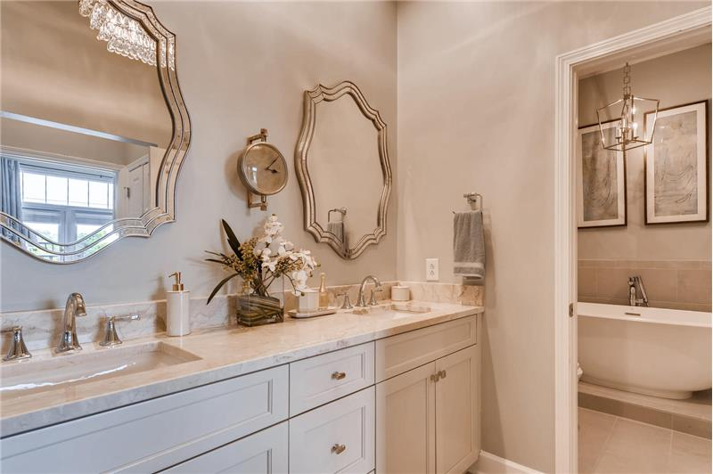 Spa-inspired, en-suite master bathroom with double-sink vanity. Custom cabinets, vanity mirrors, designer chandelier.