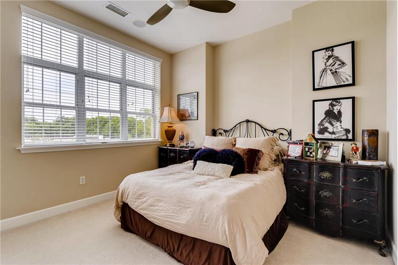 Bright and sunny secondary bedroom features a walk-in, custom closet and ceiling fan with light fixture.