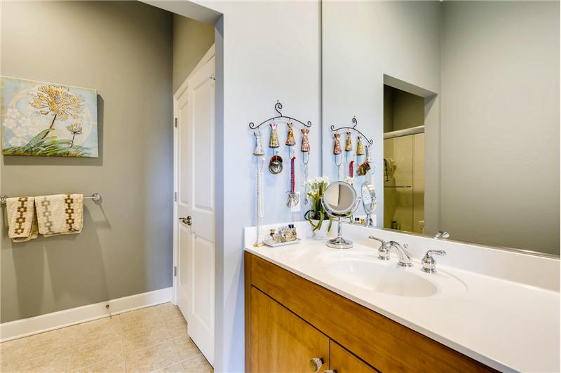 Bathroom features an expansive vanity with storage below, large utility closet, new toilet, tile flooring.