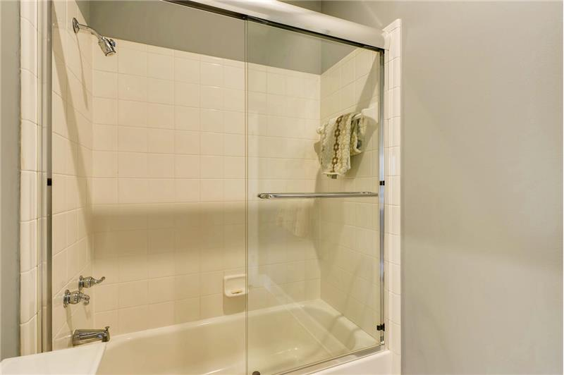 Tub/shower combination with new glass door in home's second full bathroom.