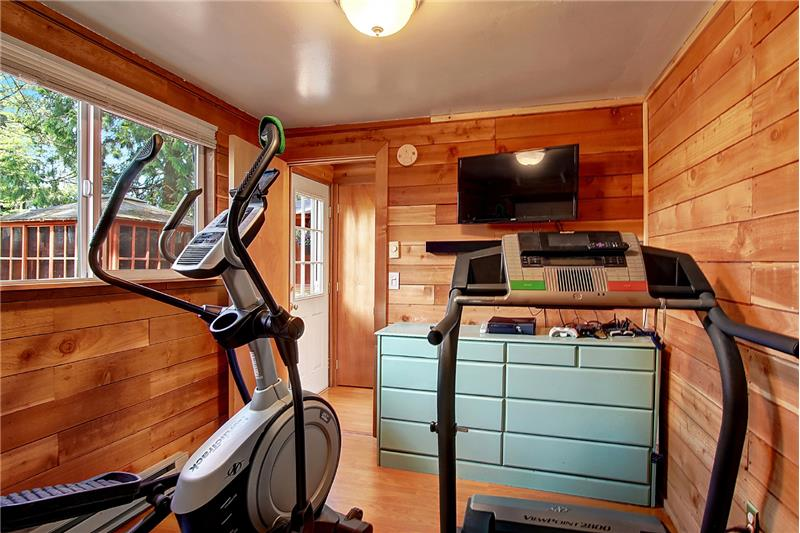 The main floor bedroom is just off the front door as well; the closet is behind the exercise equipment