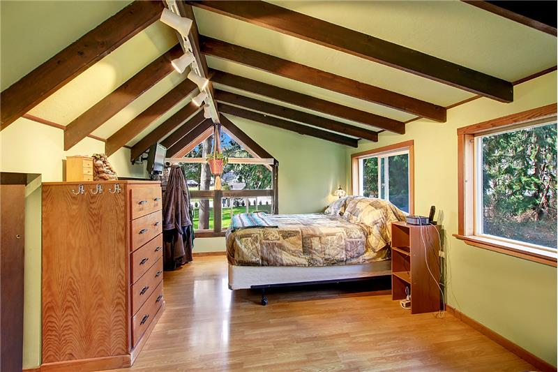 Exposed beams continue in loft bedroom. Plenty of room for a king-sized bed. Closet space is across from bed.