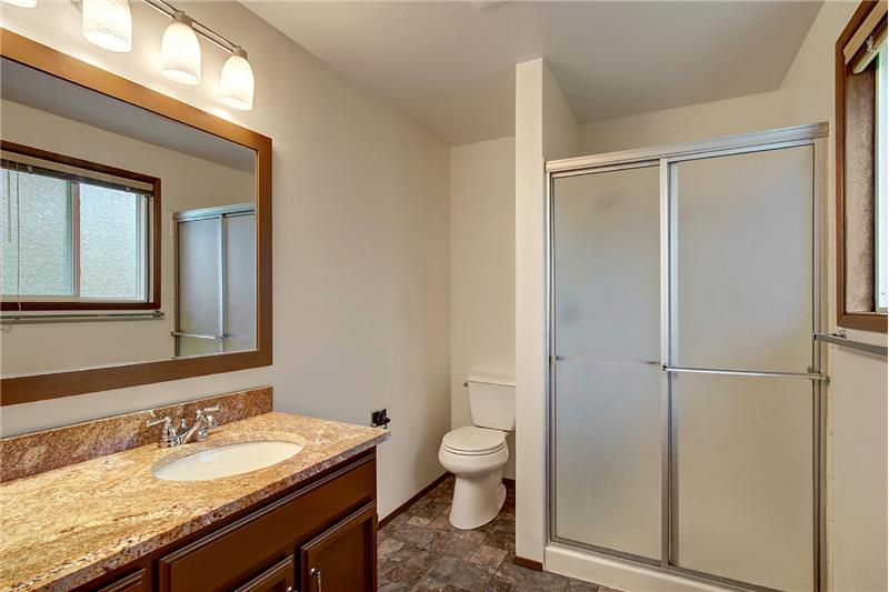 Owner Suite 3/4-Bath updated in 2016 with Kohler low-flow toilet, granite counter, undermount sink, new faucet & light fixture.