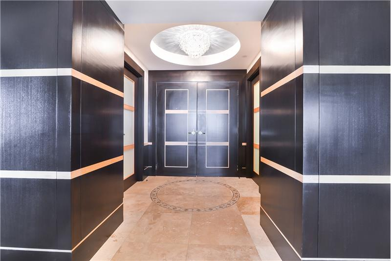 The private foyer entrance has gold design trim with wood in-lays and hidden built-in cabinets offering hidden space.