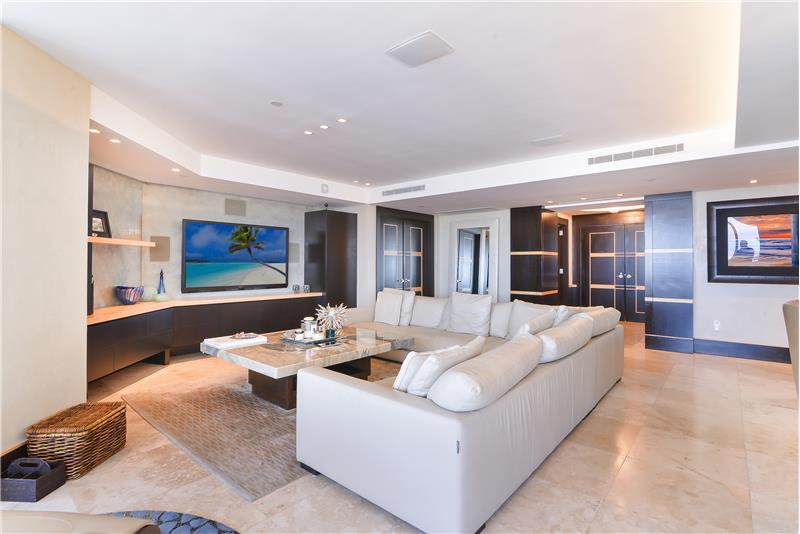 Matching Italian Botoccino marble coffee table with built-in entertainment shelves and Roche Bobois furniture.