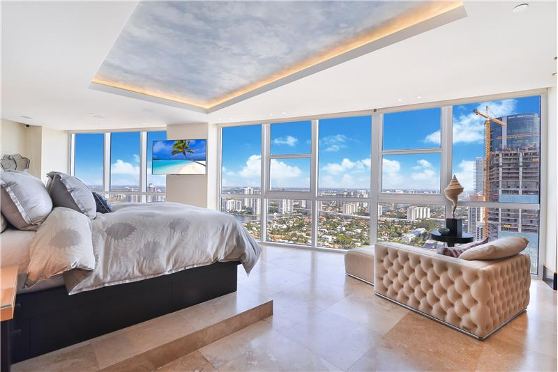 This elegant master bedroom has a floating bed and super views to the glimmering lights at night.