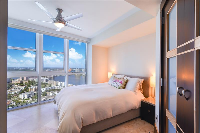 The 2nd bedroom has matching marble end tables, its own private bathroom and pretty water views over Biscayne Bay and the City.