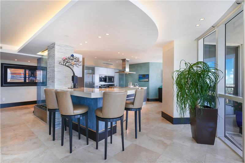 Open kitchen with marble countertops & bar area allowing the family to easily connect.