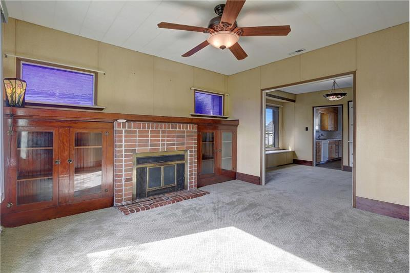 Living room with wood fireplace; glass enclosed shelves. Classic tall baseboards also carried in the dining room & bedrooms.