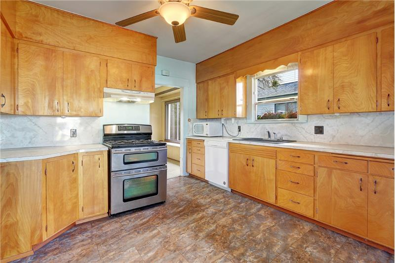 Propane 5-burner range with 2 ovens; microwave stays. New dishwasher;  ceiling fan. Looking at kitchen from Sunroom/Utility room