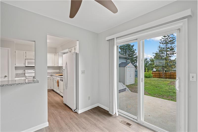 Dining room next to kitchen has sliding glass door to backyard