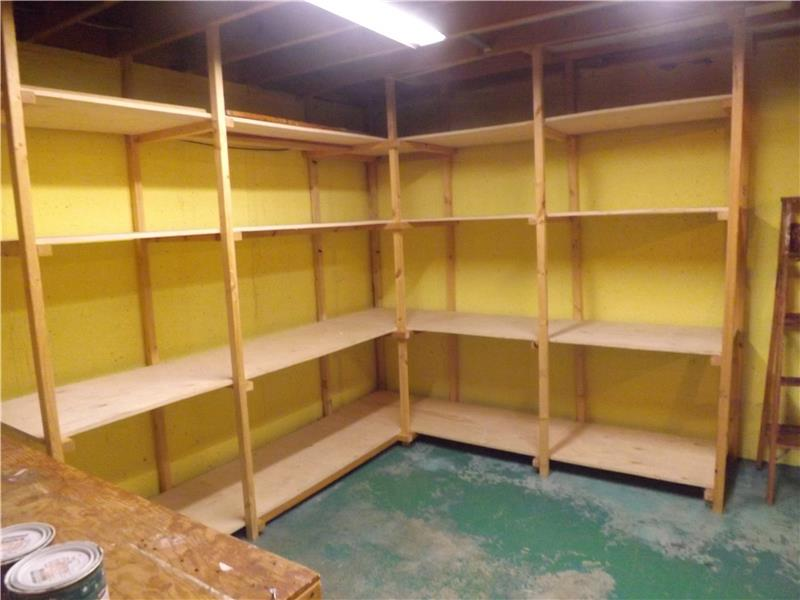 Lots of storage shelving in unfinished part of basement (workbench visible at left)