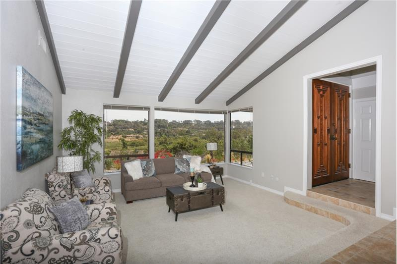 Large living room with vaulted ceilings and a view.