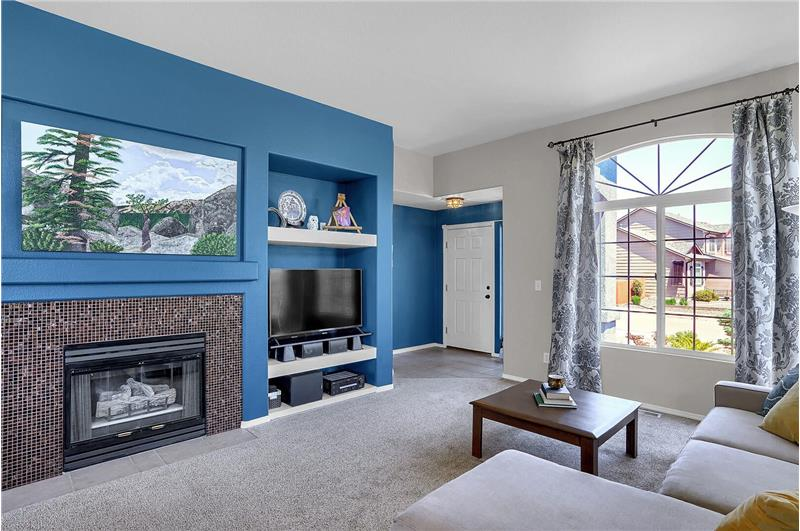 Tiled entry into the formal Living Room which features a large view window with gorgeous window covers and a gas-log fireplace