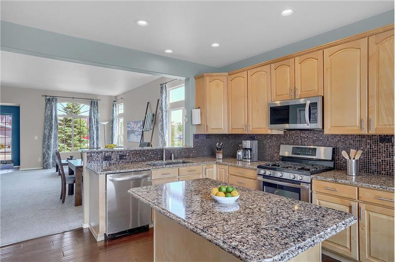 The island Kitchen features cabinets with quartz countertops and attractive glass tile backsplash