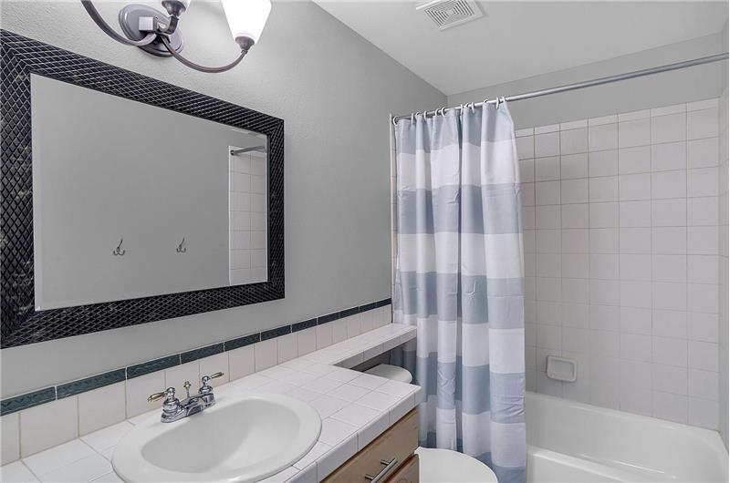 The main level hall Bathroom includes a vinyl plank floor, vanity, framed mirror, and tiled tub/shower