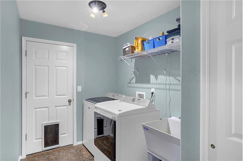 The main level Laundry Room has convenient garage access and features a vinyl floor, utility sink, and washer/dryer that stay