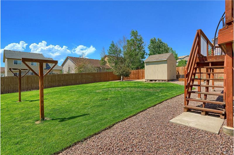 The deck has stairs to the fenced level lot that hosts a storage shed and clothes line