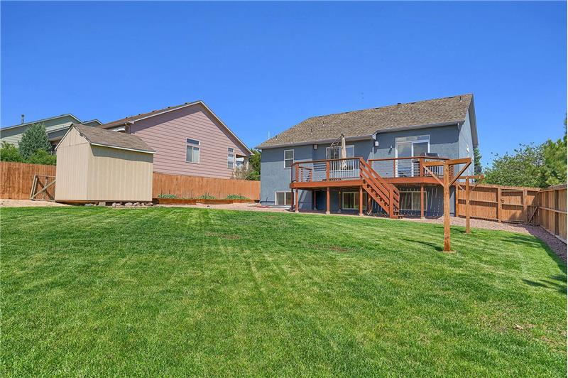 Beautifully landscaped, quarter-acre, level fenced lot with auto sprinklers, a deck, storage shed, and lush green grass