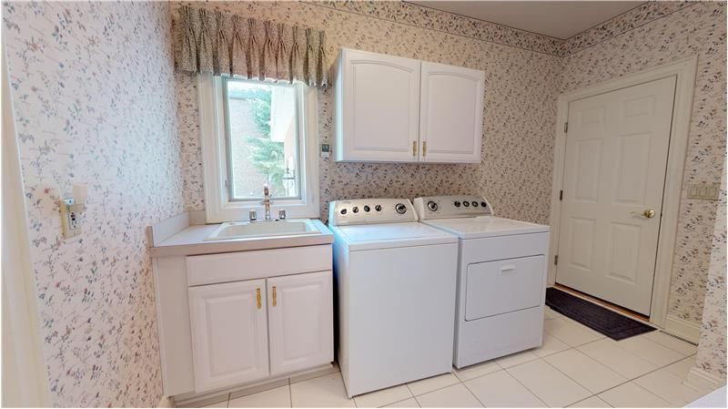 First floor laundry room includes the washer and dryer and has lots of cabinets for storage!