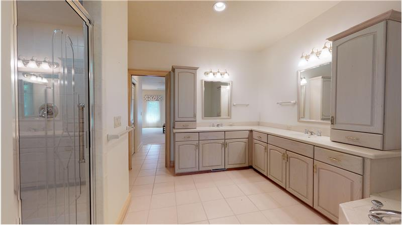 Master bath with double vanities, jacuzzi tub, and tiled shower!