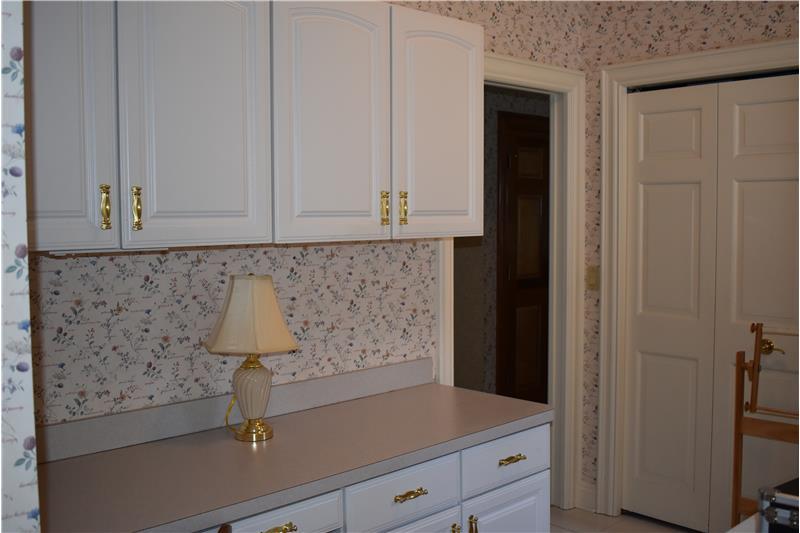 Cabinets opposite the washer and dryer.