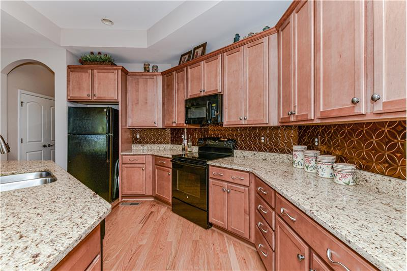 Well-appointed kitchen with expansive granite counters, decorative back-splash, trey ceiling, recessed lights, roll-out shelves.