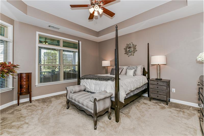 Serene and spacious master bedroom with trey ceiling overlooks the screened porch and deck.