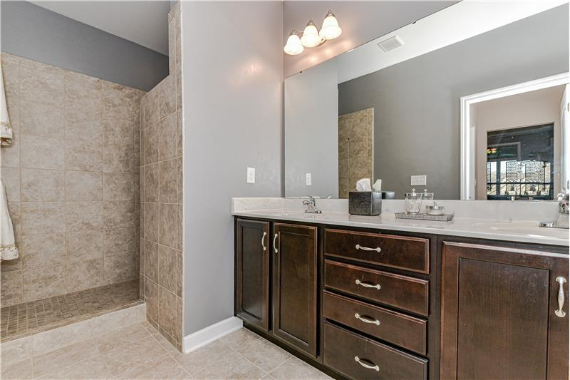 En-suite master bathroom features double sink vanity, tile flooring, private WC, and over-sized, step-in Roman-style shower.