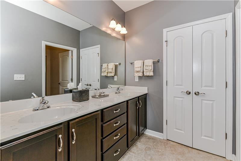 Master bathroom's expansive double-sink vanity provides lots of storage space. Neutral decor provides a soothing atmosphere.