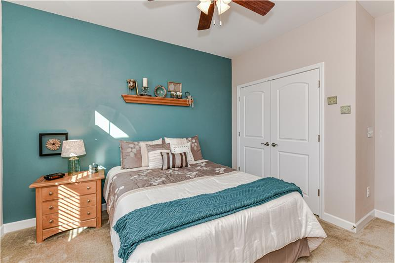 Guest bedroom features a double closet and ceiling fan with light.
