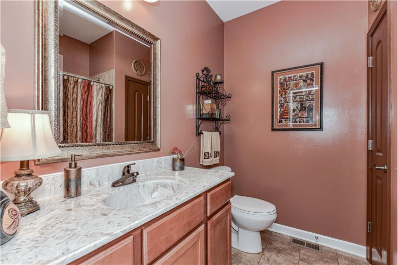 Guest bathroom provides a good sized vanity with storage, tile flooring, closet, and tub/shower combination.