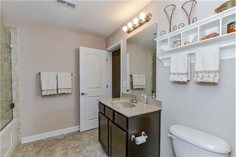 Full, en-suite bathroom in finished basement with neutral finishes.