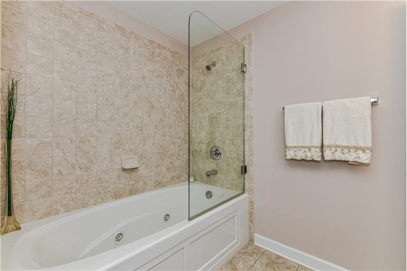 Basement level bathroom features a 6 foot whirlpool tub with tile surround, custom, frame-less glass enclosure.