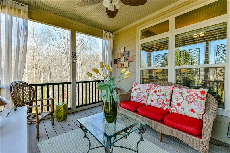 Charming and cozy screened porch overlooks the woods in the back of the home.