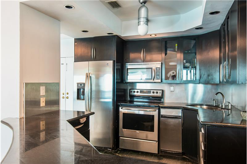 Open kitchen with black granite & stainless steel appliances.