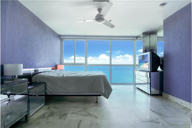 Bedroom 1 with floor to ceiling glass & ocean views.