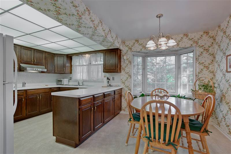 The kitchen and eating area combine for a great family gathering center with its serene views of the lovely backyard.
