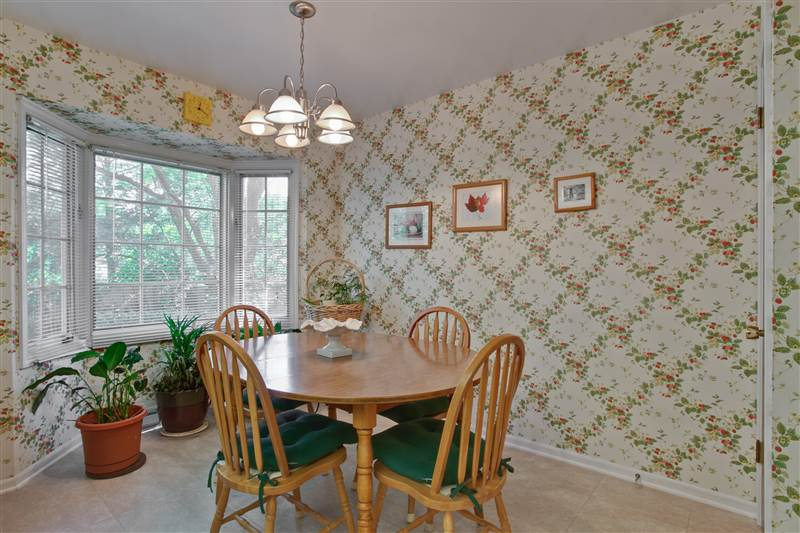 Adjoining the kitchen prep center, the eating area features a pretty bay window that overlooks the quiet backyard.