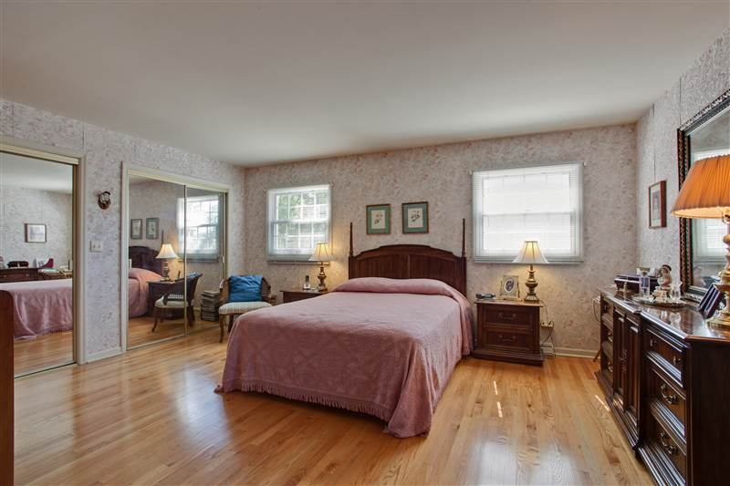 Double doors open into this spacious master bedroom with gleaming oak hardwood flooring, three double-door closets and sunny sou