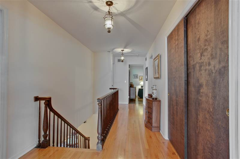 The wide, loft-like upper hallway leads to three spacious family bedrooms and a large compartmented family bath. It additionally