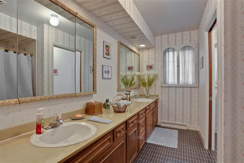 The second floor family bath boasts a large, long vanity with twin sinks and a separate commode room.