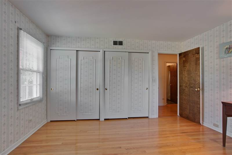 With convenient across-the-hall access to the shared family bath, the northwest bedroom boasts two double-door closets.