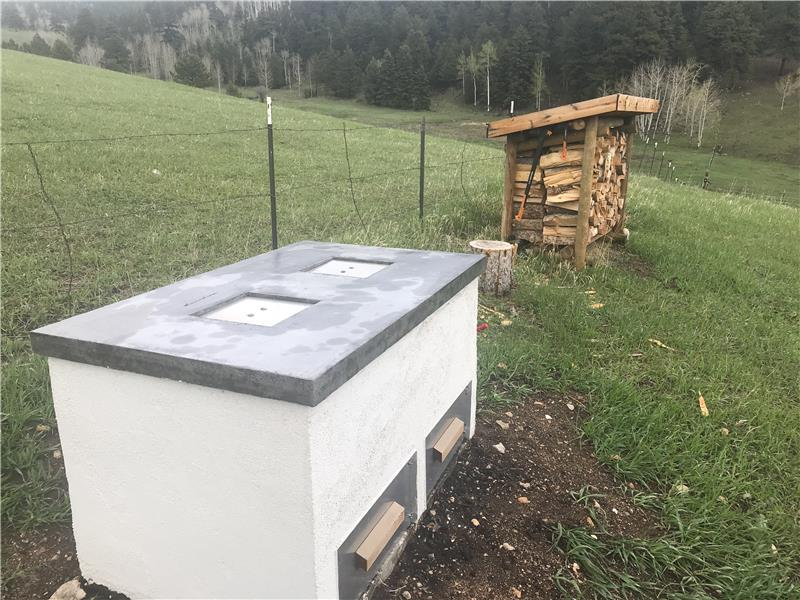 Two-compartment bear-proof composting unit with wood shed beyond