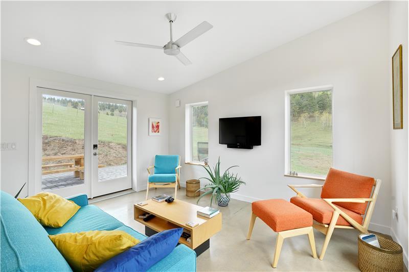 Living room has door to back patio/outdoor kitchen