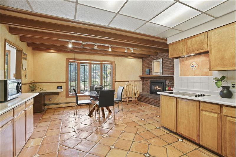 Country-style kitchen has bay window, large eating area and fireplace. Cozy!